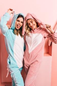 Mulheres alegres em pijamas divertidas posando no fim de semana