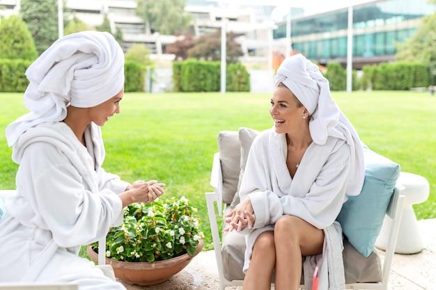 Mulheres alegres em roupões de banho, bebendo amigos de suco em salão de spa. retrato de uma mulher feliz e alegre em