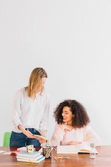 Mulheres alegres estudando juntos na mesa