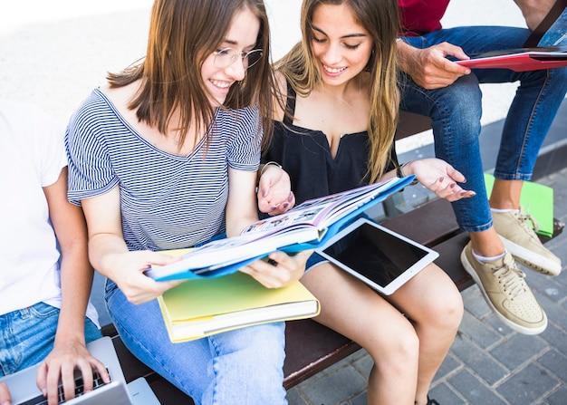 Mulheres alegres estudando no banco perto de amigos