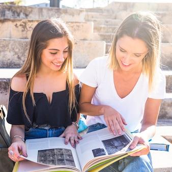 Mulheres alegres, lendo o livro sobre as etapas