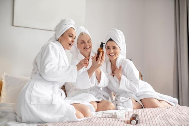 Mulheres alegres na cama olhando um produto cosmético