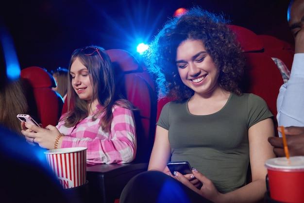 Mulheres alegres novas que sorriem usando seus telefones espertos ao sentar-se no auditório do cinema que olha uma atividade de entretenimento da juventude da amizade da comunicação da conexão da mobilidade da tecnologia do filme.