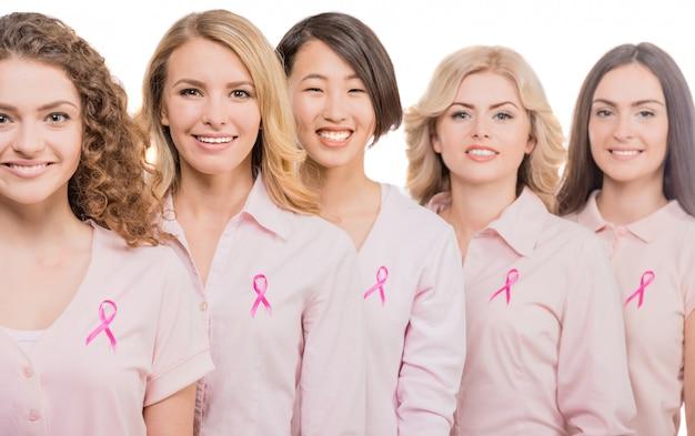 Mulheres alegres que vestem fitas cor-de-rosa para apoiar o peito.