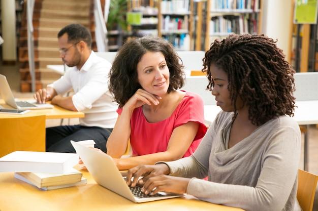 Mulheres alegres, trabalhando com o laptop na biblioteca pública