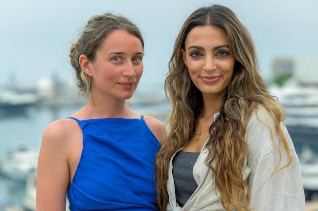 Mulheres amigas em barcelona, espanha. posando perto do porto