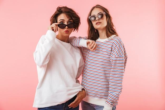 Mulheres amigas isoladas sobre posando de parede rosa.