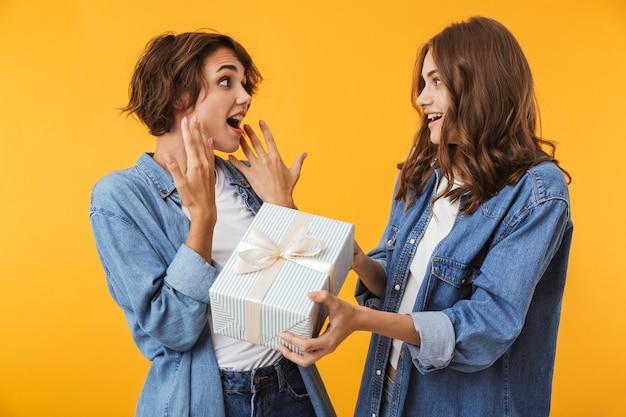 Mulheres amigas isoladas sobre uma parede amarela segurando uma caixa de presente surpresa.