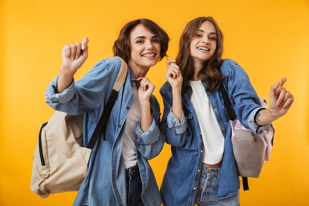 Mulheres amigas isoladas sobre uma parede amarela, usando telefone celular, ouvindo música com fones de ouvido.
