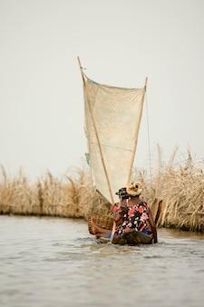 Mulheres andando de barco na lagoa da aldeia de palafitas ganvie no benin.