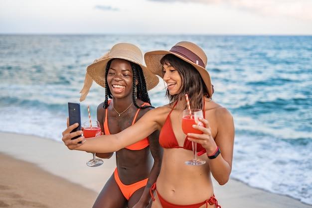 Mulheres animadas e diversificadas tirando autorretrato na praia