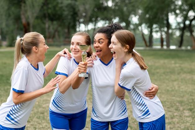 Mulheres animadas segurando uma taça de ouro