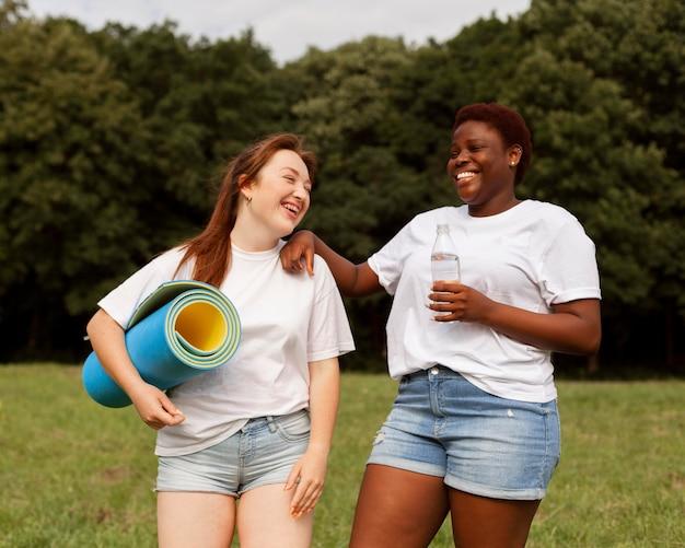Mulheres ao ar livre segurando uma garrafa de água e um tapete de ioga