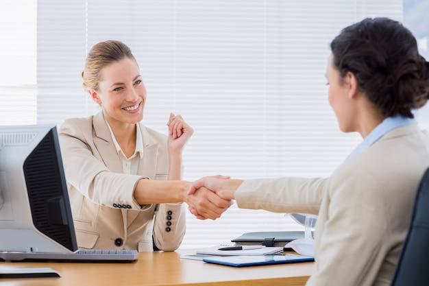 Mulheres apertando as mãos em uma reunião de negócios