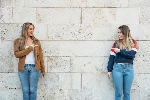 Mulheres apontando para o outro