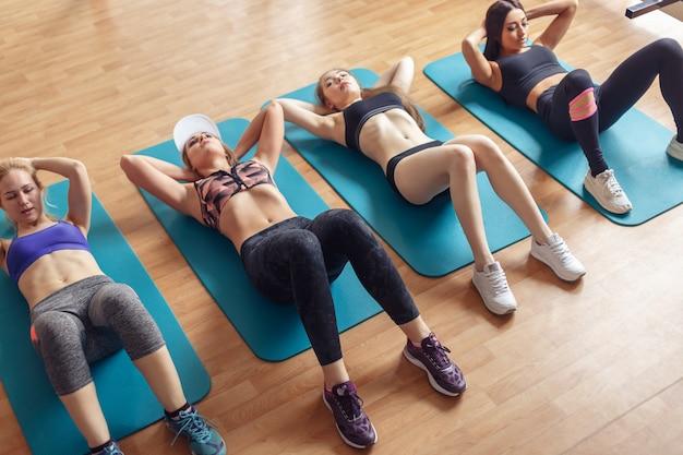Mulheres aptas a fazer abdominais em colchonetes no clube de fitness