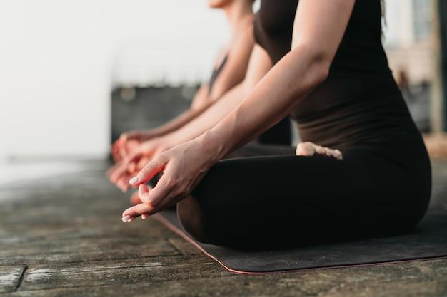 Mulheres aptas cortadas meditando ao ar livre no tapete de ioga