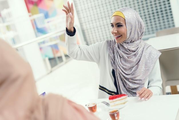 Mulheres árabes novas que sentam-se na alameda com amigo.