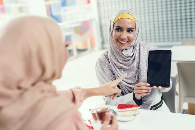 Mulheres árabes que sentam-se no café na alameda com tabuleta.