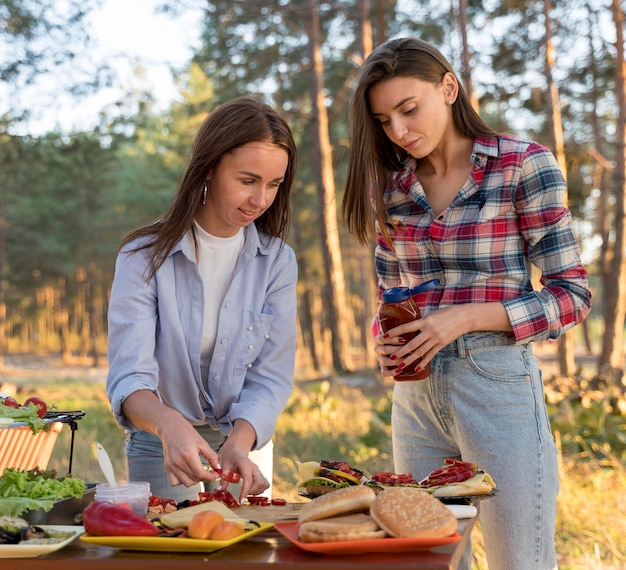 Mulheres arrumando comida na mesa para amigos