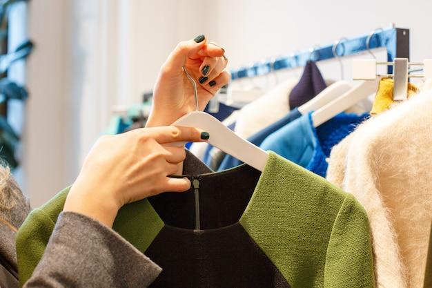 Mulheres às compras no shopping da moda, escolhendo roupas novas