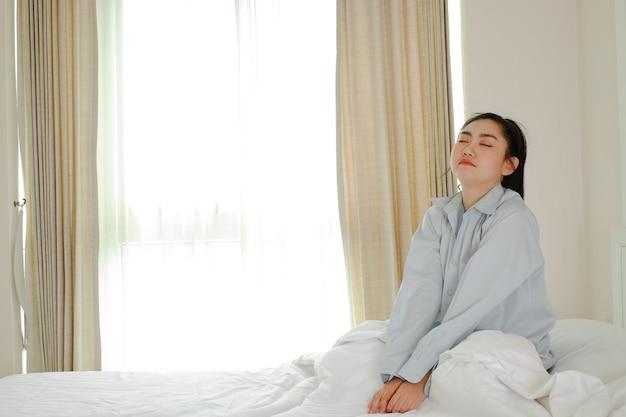Mulheres asiáticas acordam em uma cama no quarto