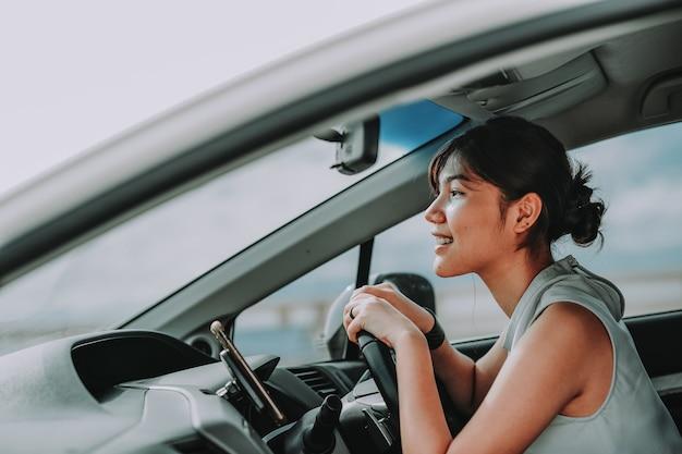 Mulheres asiáticas atraentes sorrindo e olhando diretamente enquanto dirigia um carro. viajar férias conceito de relaxamento e aproveitamento.