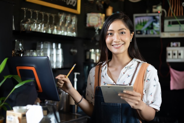 Mulheres asiáticas barista sorrindo e usando a máquina de café no balcão da loja de café