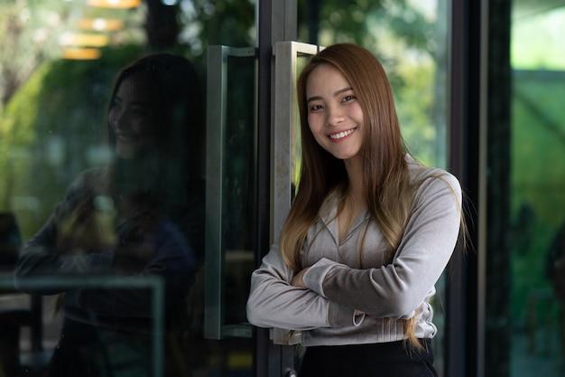 Mulheres asiáticas bonitas, mulheres de funcionamento, estando de sorriso na frente do escritório