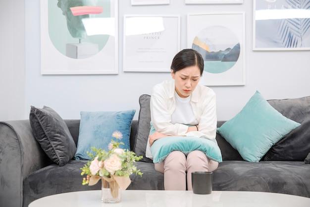 Mulheres asiáticas, com dores de estômago, ela acorda no meio da noite enquanto dorme