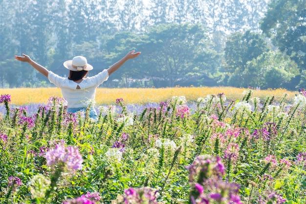 Mulheres asiáticas com flor desabrochando no jardim. prado floral fresco da primavera e do verão.