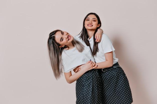 Mulheres asiáticas com saias e blusas idênticas posando em uma parede bege