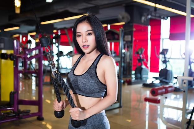 Mulheres asiáticas da aptidão que executam fazendo exercícios que treinam com máquina de remo