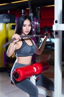 Mulheres asiáticas da aptidão que executam fazendo exercícios que treinam os músculos do ombro e da caixa no interior e no health club do gym do esporte