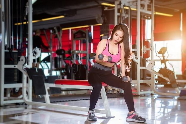 Mulheres asiáticas de aptidão realizando fazendo exercícios de treinamento com haltere esporte no ginásio backgr