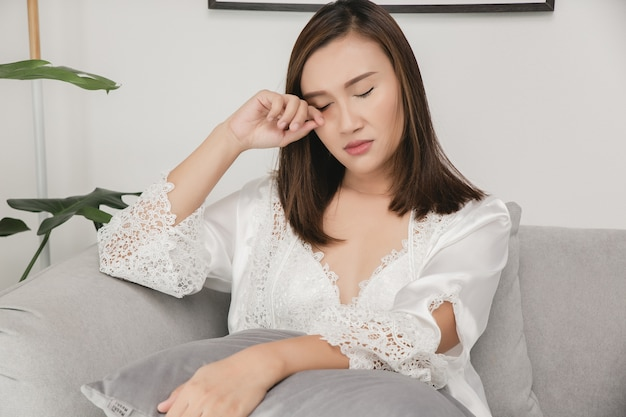 Mulheres asiáticas de camisola e roupão de cetim branco esfregando os olhos sentadas no sofá cinza