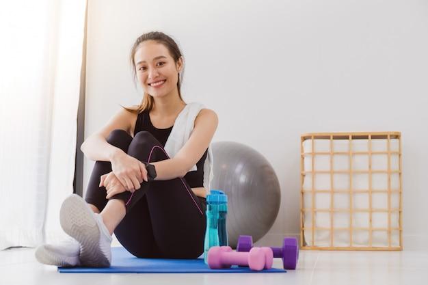 Mulheres asiáticas descansando depois de jogar ioga e exercer em casa
