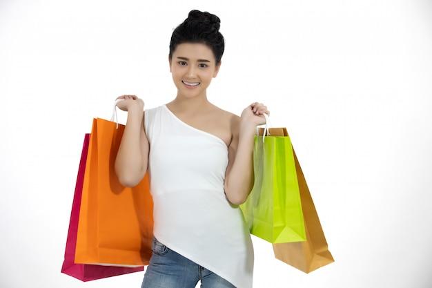 Mulheres asiáticas e linda garota está segurando sacolas de compras e sorrindo