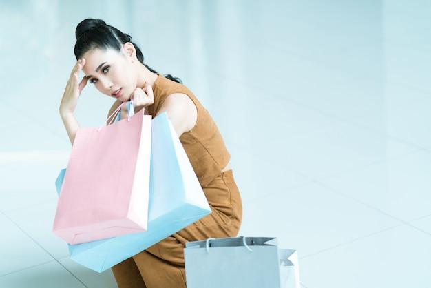 Mulheres asiáticas ela se sentia estressada e cansada de comprar. no shopping