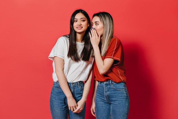 Mulheres asiáticas em camisetas largas fofocando na parede vermelha