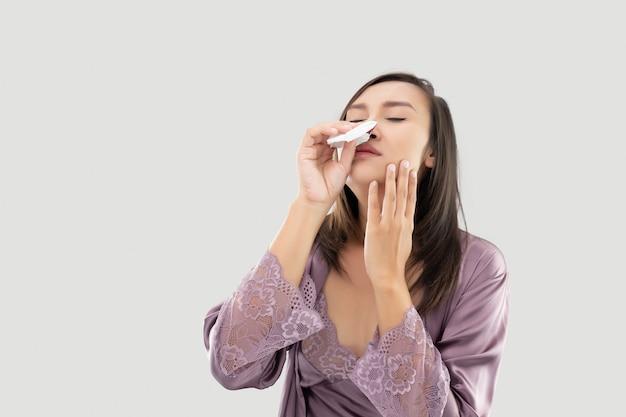 Mulheres asiáticas em pijamas de cetim com hemorragia nasal no cinza