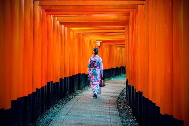 Mulheres asiáticas em quimonos japoneses tradicionais no santuário fushimi inari em kyoto, japão.