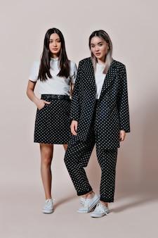 Mulheres asiáticas em trajes de bolinhas olhando para a frente na parede bege