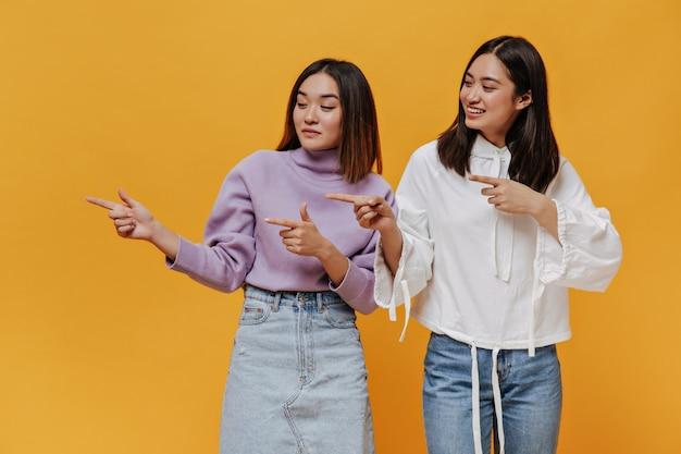 Mulheres asiáticas encantadoras em trajes de jeans apontam para a esquerda no lugar para texto isolado