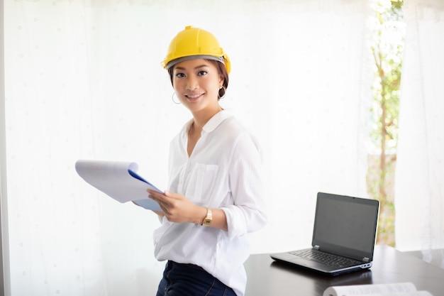 Mulheres asiáticas engenharia de inspeção e trabalho e segurando plantas no escritório. ela está sorrindo feliz pelo trabalho