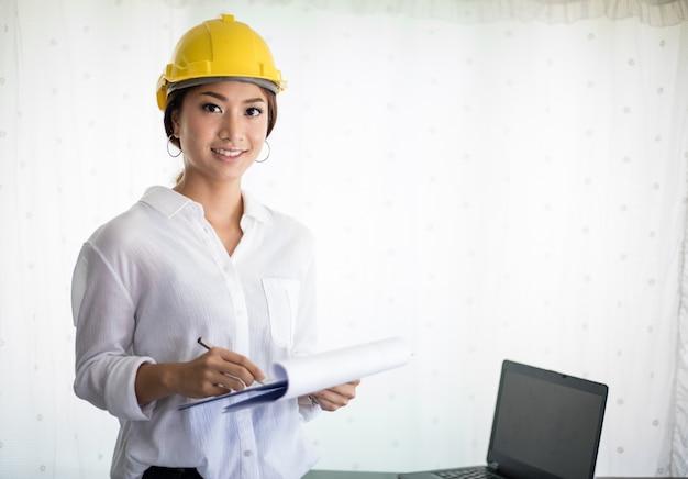Mulheres asiáticas engenharia de inspeção e trabalho e segurando plantas no escritório