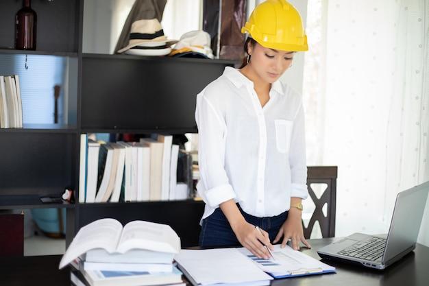 Mulheres asiáticas, engenharia, inspecionando, e, trabalhando, e, segurando, desenhos técnicos, em, escritório