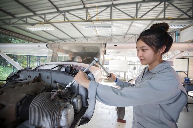 Mulheres asiáticas engenheiros e técnicos estão consertando aeronaves.