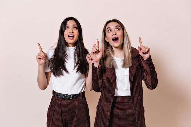 Mulheres asiáticas erguem os olhos com surpresa e apontam o dedo para o local do texto na parede bege
