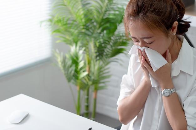 Mulheres asiáticas espirrando e com frio. ela está no escritório.